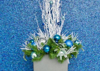 Container with white twig greens and blue and silver decor