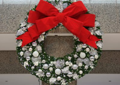 Wreath with silver and white decor and red bow